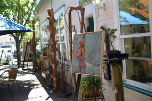 Speidel painting of woman in red on an easel in the sculpture garden of Graton Gallery